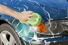 Washing car. Closeup image of a hand with a soapy sponge washing a vehicle Royalty Free Stock Photo