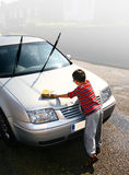 Washing the car. Young boy helps washing the car on a beautiful summer's day. Concept of helpfulness and determination Stock Photo