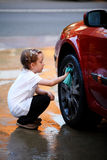 Washing the car. Young girl washing the wheel of a red car stock image