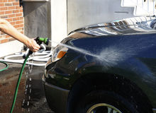 Washing a car. Woman's hand with a hose washing a car Stock Images