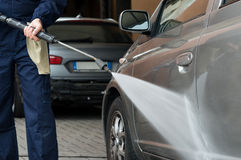 Washing Car. Closeup Of A Mechanic Washing A Car By Pressured Water At Garage Royalty Free Stock Photography