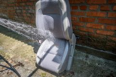 Washing the car seat at home by spraying water from the hose royalty free stock photography