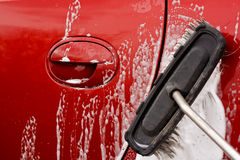 Cleaning the car with a brush Royalty Free Stock Image