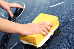 Washing Car. Young male hand washing a dark car with a yellow sponge Royalty Free Stock Photography