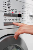 Washing clothes. A female hand is pressing a button on a washing machine Stock Image