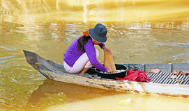 Washing Clothes On the River. Vietnamese woman sitting in a boat Stock Image