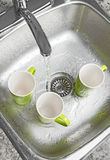 Washing cups in the kitchen sink. Washing green cups in the kitchen sink. Water running from the tap royalty free stock photos