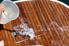 Washing The Deck. With water throwed from a plastic buket Royalty Free Stock Images