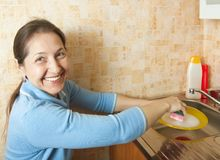 Washing dirty dishes. Woman washing dirty dishes in the kitchen sink Stock Photography