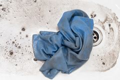 Washing dirty rags for cars in the water.  Stock Image
