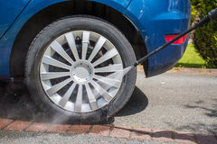 Washing a dirty wheel with a high pressure jet wash Stock Image