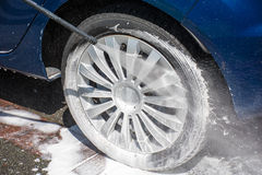 Washing a dirty wheel with a high pressure jet wash Royalty Free Stock Photo