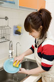 Washing dishes. Young woman washing dish in kitchen Royalty Free Stock Image