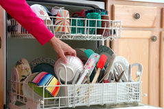 Washing Dishes. A female hand is shown loading dishes into the dishwasher Royalty Free Stock Image