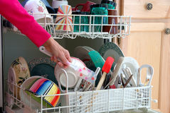 Washing Dishes. A female hand is shown loading dishes into the dishwasher Stock Image