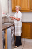 Washing dishes. A happy blonde senior woman washing dishes in kitchen wearing an apron Royalty Free Stock Images