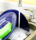 Washing dishes. A sink full of dishes in soapy water with the kitchen faucet running Stock Images