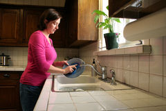 Washing Dishes. A woman washes dishes at the kitchen sink Royalty Free Stock Photo