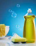 Washing dishes. Dish washing products with bubbles, soap and crockery Royalty Free Stock Photos