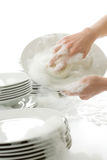 Washing dishes - hands with gloves in kitchen Royalty Free Stock Photos