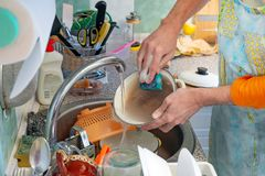 Washing Dishes in Kitchen. A man is washing dishes in kitchen. He is using a sponge and dishwashing product. Hot water flows from the tap royalty free stock photos