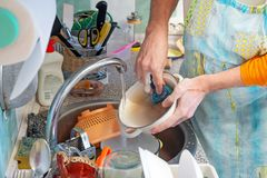 Washing Dishes in Kitchen. A man is washing dishes in kitchen. He is using a sponge and dishwashing product. Hot water flows from the tap royalty free stock photography