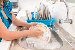 Washing the dishes in the kitchen sink stock photo