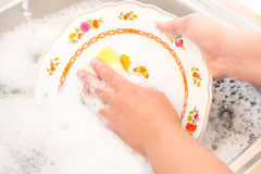 Washing the dishes on the kitchen sink Royalty Free Stock Image