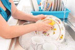 Washing the dishes on the kitchen sink. House chores - Washing the dishes on the kitchen sink royalty free stock photography