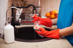 Washing the dishes after a meal - child hands scrubbing a glass, Stock Images