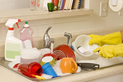 Hands washing dirty dishes. Hands in yellow rubber gloves washing sink full of dirty dishes royalty free stock photos