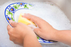Washing the dishes on soapy water Royalty Free Stock Image