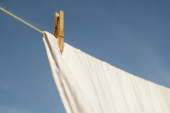 Washing Drying on a Line. A white sheet drying on a washing line against a blue sky Stock Images