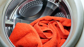Washing drying machine with red towel in laundry. Washing or drying machine with red towel in a laundry. Household equipment and cleanliness hygiene housework royalty free stock image