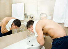 Washing face. Attractive man washing face in hotel bathroom Royalty Free Stock Photos