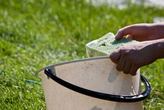 Washing. Female hands holding a bucket with some washing liquid and sponge, outdoors Stock Photo