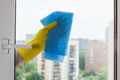 Washing glass of home window by blue rag. Washing glass of home window in urban apartment house by blue rag royalty free stock photo