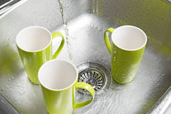 Washing green cups in the kitchen sink. Washing bright green cups in the kitchen sink. Water running from the tap royalty free stock image