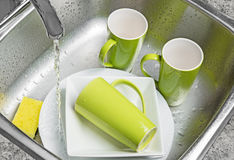 Washing green cups and plates in the kitchen sink. Washing green cups and white plates in the kitchen sink. Water running from the tap stock image