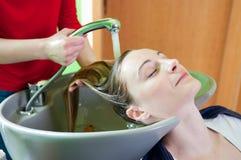 Washing hair. Woman washing hair in hair salon Stock Photography