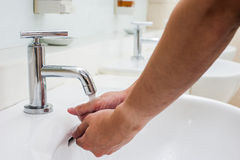 Washing hand in faucet in restroom Royalty Free Stock Photo