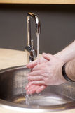 Washing Hands. Male hands washing under running water Royalty Free Stock Image