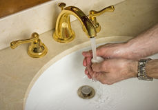 Washing hands. Man washing hands with soap under running water Stock Image