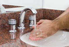 Washing hands. In a bathroom sink Royalty Free Stock Images