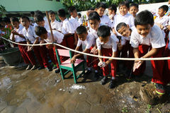 Washing hands. Elementary school students are washing their hands before entering school in the city of Solo, Central Java, Indonesia royalty free stock images