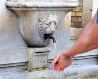 Washing hands with history. Man washes hands at fountain in Vatican gardens, Rome Royalty Free Stock Photo