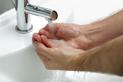 Washing hands with soap. Under running water an a white sink stock images