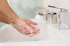 Washing hands with soap under running water at bathroom sink Stock Photo