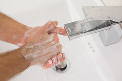 Washing hands with soap under running water Stock Photos