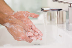 Washing hands with soap under running water royalty free stock images
